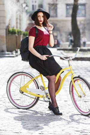 Beautiful girl in burgundy shirt, black skirt and hat with bag sitting on bicycle. Looking at camera. Full body. Cycling, outdoor, city 写真素材