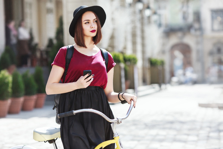 Beautiful girl in burgundy shirt, black skirt and hat with bag sitting on bicycle. Holding phone, looking aside. Cycling, outdoor, city