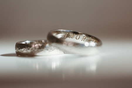 Pre-wedding preparation. Two silver wedding rings for weds. Inscription Amor from inner side. Closeup, no people