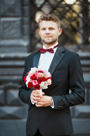 Wedding photo shooting. Bridegroom standing with bouquet.  Man wearing white shirt, black jacket and bow-knot. Outdoor
