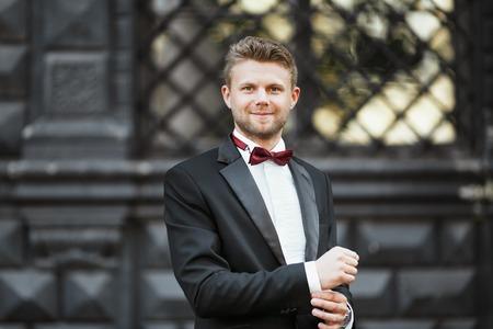 Wedding photo shooting. Bridegroom standing outdoor. Man wearing white shirt, black jacket and bow-knot. Waist up, looking at camera
