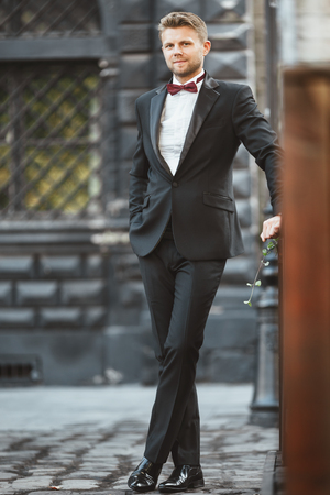 Wedding photo shooting. Bridegroom standing outdoor. Man wearing white shirt, black jacket, bow-knot and black shoes. Full body