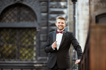 Wedding photo shooting. Bridegroom standing outdoor and smiling. Man wearing white shirt, black jacket and bow-knot. Waist up, looking at camera 写真素材