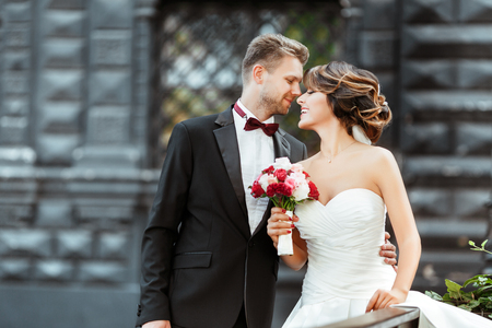 Wedding photo shooting. Bride and bridegroom standing with bouquet. Looking at each other and smiling. Woman wearing white dress and veil and man wearing suit. Outdoor, waist up, profile 写真素材