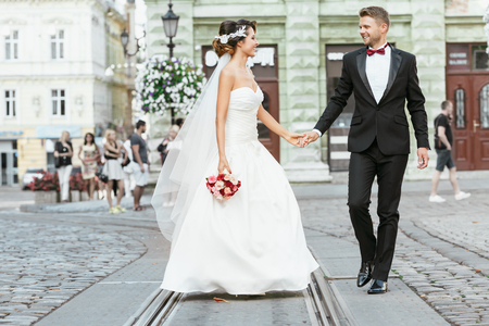 Wedding photo shooting. Bride and bridegroom walking in the city. Married couple holding hands of each other and bouquet. Outdoor, full body 写真素材