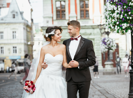 Wedding photo shooting. Bride and bridegroom walking in the city. Man embracing his bride. Looking at each other. Holding bouquet. Outdoor, profile