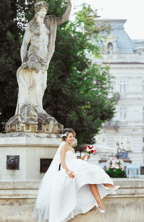 Wedding photo shooting. Bride sitting near monument in the city. Holding bouquet and smiling, looking aside. Wearing white dress, white shoes and veil. Outdoor, full body