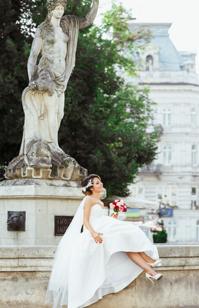 Wedding photo shooting. Bride sitting near monument in the city. Holding bouquet and smiling. Wearing white dress, white shoes and veil. Outdoor, full body, profile