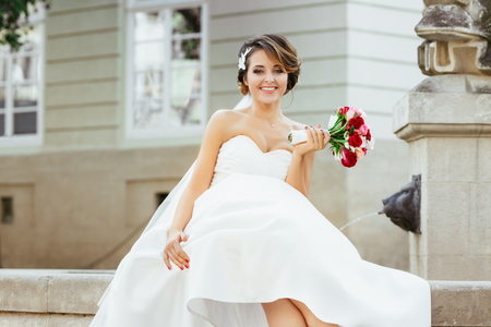 Wedding photo shooting. Bride sitting near monument in the city. Holding bouquet, looking at camera and smiling. Wearing white dress, white shoes and veil. Outdoor, closeup