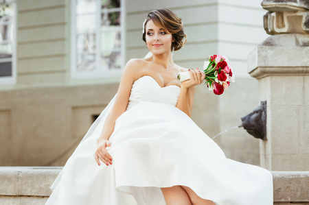 Wedding photo shooting. Bride sitting near monument in the city. Holding bouquet, looking aside. Wearing white dress, white shoes and veil. Outdoor, closeup