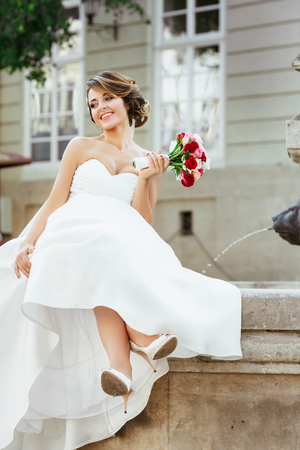 Wedding photo shooting. Bride sitting near monument with crossed legs. Holding bouquet, smiling and looking aside. Wearing white dress and veil. Outdoor, full body
