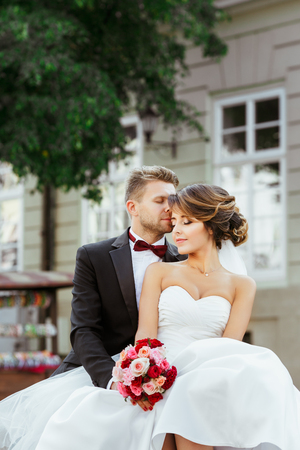 Wedding photo shooting. Bride and groom sitting near monument. Holding bouquet, both with closed eyes. Bridegroom kissing bride's forehead. Outdoor