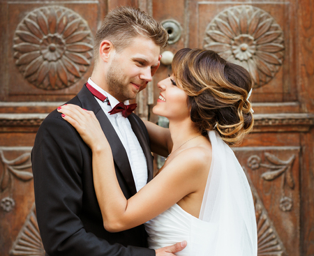 Wedding photo shooting. Bridegroom and bride standing near wooden door and embracing each other. Outdoor, waist up, closeup