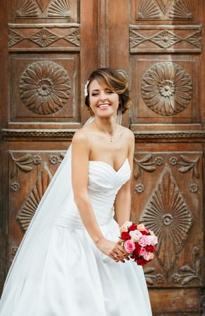 Wedding photo shooting. Bride standing near wooden door and smiling. Wearing white dress and veil and holding bouquet. Outdoor