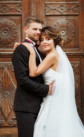 Wedding photo shooting. Bridegroom and bride standing near wooden door and embracing each other. Outdoor