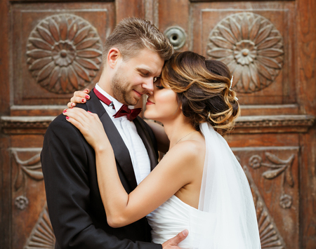 Wedding photo shooting. Bridegroom and bride standing near wooden door and embracing each other. Very close to each other. Outdoor, waist up, closeup