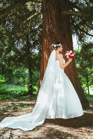 Wedding photo shooting. Bride standing in pine forest near tree with bouquet. Wearing white dress and long veil. Outdoor, full body, profile