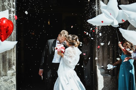 Wedding ceremony. Bride and groom embracing near church and smiling. A lot of flowers, confetti and balloons. Guests around. Outdoor