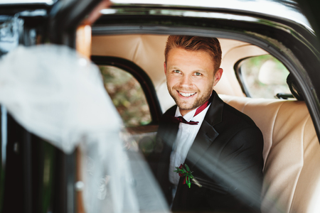 Wedding day. Bridegroom sitting in wedding car, looking at camera and smiling. Decorations. Sunny day. Waist up, closeup
