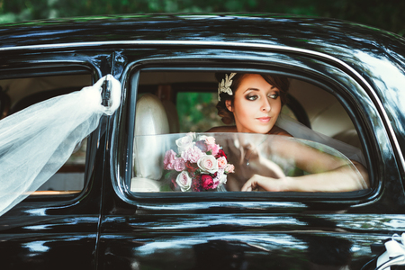 Wedding day. Bride sitting in wedding car, looking at window and holding bouquet. Decorations. Waist up Standard-Bild