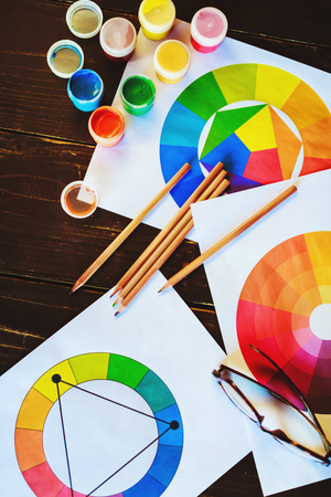Colorful paints, brushes, pencils, drawings and glasses on dark wooden table, point of view.