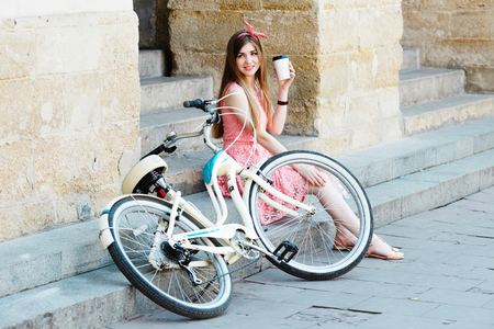 girl with a cup of coffee and vintage bicycle 写真素材