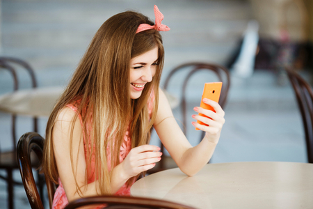 girl smiling and looking at mobile phone