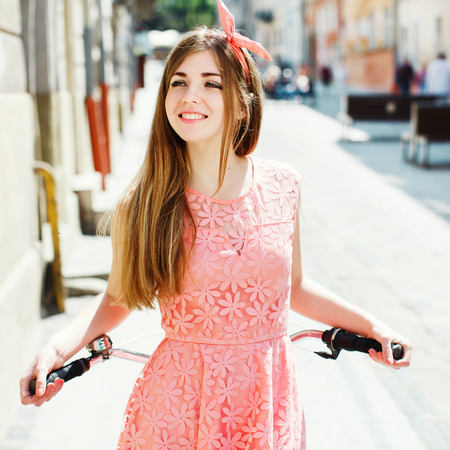 girl smiling and holding a bicycle handlebar