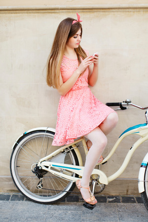 girl sitting on vintage bicycle and using smartphone