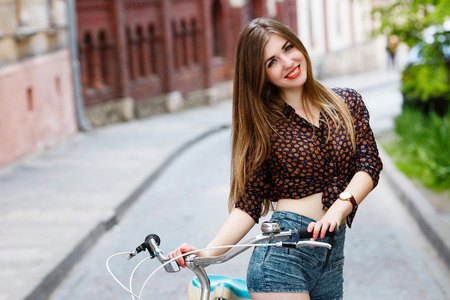 Young girl with bicycle standing on the street