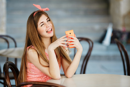 girl with smart phone showing tongue and winks