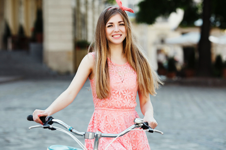 blond-brown girl smiling and holding bicycle. Standard-Bild