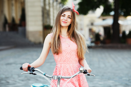 Pretty blond-brown girl holding bicycle.