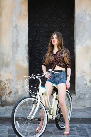 Pretty girl is sitting on bicycle on the street of old city Standard-Bild