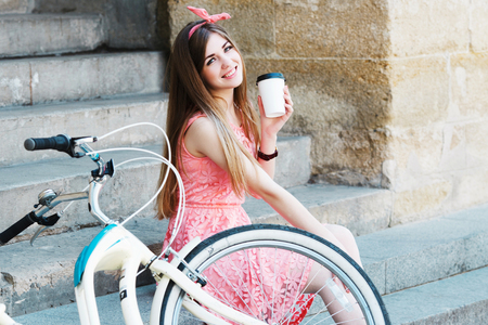 girl smiling with a cup of coffee and vintage bicycle