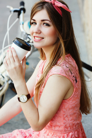 girl smiling with a cup of coffee, close-up Standard-Bild