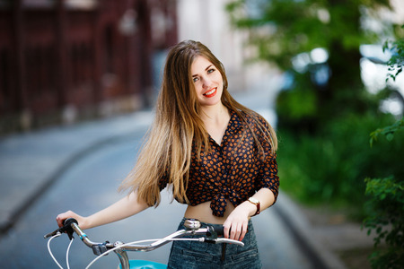 Girl is standing on the street with bicycle and smiling