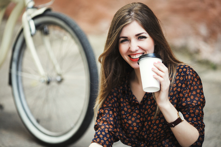 Smiling girl is drinking coffee on tiled pavement in old city