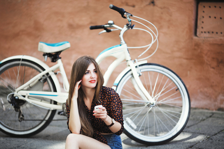 Beautiful girl with long straight hair is sitting on tiled pavement in old city
