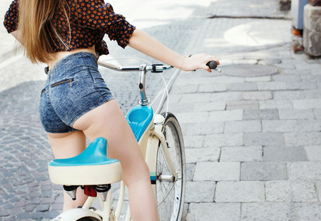 Rear view of girl with long hair is sitting on the bicycle in ol Imagens