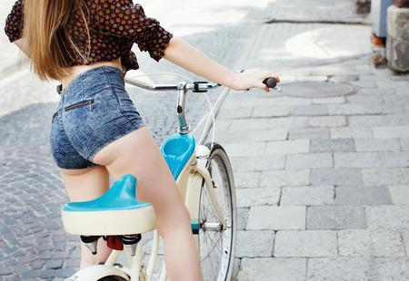 Vista trasera de la niña con el pelo largo está sentada en la bicicleta en ol Foto de archivo