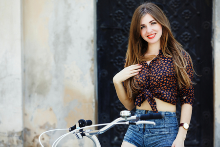 Happy young woman with long hair is sitting on the bicycle and looking at the camera on the street
