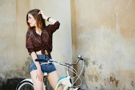 Pretty young woman with long hair is sitting on the bicycle on the old wall background