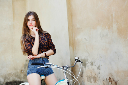Nice girl with long hair is posing on the bicycle on the old wall background