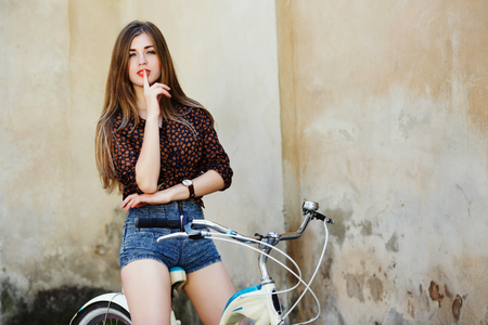 Passionate young woman with long hair is posing on the bicycle on the old wall background Standard-Bild