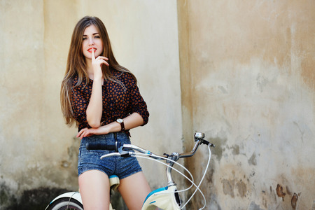 Smiling young woman with long hair is posing on the bicycle on the old wall background