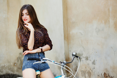 Adorable girl with long hair is posing on the bicycle on the old wall background