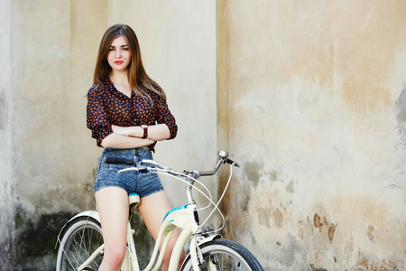 Attractive young woman with long hair is posing on the bicycle on the old wall background