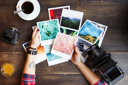 Top view of womens hands holding printed photos