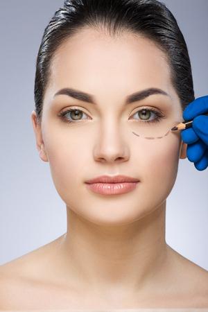 Plastic surgeon drawing line under eye